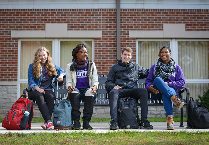 Students sit on Relationship Bench